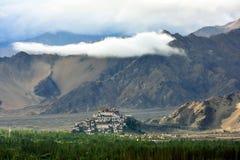 Den buddistiska kloster Tiksi i mitt av den Indus dalen, gröna träd nära flodsängen, låga moln ligger på bergen, Ladak Arkivbild