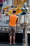 Den buddistiska mannen ber, nära stor shoppinggalleria, Bangkok Royaltyfria Foton