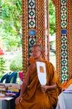 Den buddistiska munken poserar för ett foto på den buddistiska templet från Damnoen Saduak som svävar marknaden Royaltyfri Bild