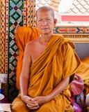 Den buddistiska munken poserar för ett foto på den buddistiska templet från Damnoen Saduak som svävar marknaden Fotografering för Bildbyråer