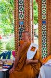 Den buddistiska munken poserar för ett foto på den buddistiska templet från Damnoen Saduak som svävar marknaden Royaltyfri Fotografi
