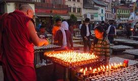 Den buddistiska munken tänder en be stearinljus, den Boudhanath stupaen, Katmandu, Nepal royaltyfri foto