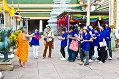 Den buddistiska munken vägleder turister i tempelområdet av Wat Pho Pho i Bangkok Royaltyfri Foto