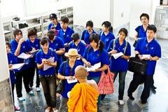 Den buddistiska munken vägleder turister i tempelområdet av Wat Pho Pho i Bangkok Royaltyfri Fotografi