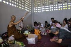 Den buddistiska munken välsignar folk som gör en stor merit Arkivfoto