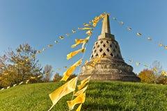Den buddistiska stupaen på en kulle som dekoreras med den buddistiska bönen, sjunker, E Royaltyfri Foto