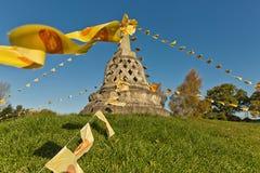 Den buddistiska stupaen på en kulle som dekoreras med den buddistiska bönen, sjunker, E Arkivbilder