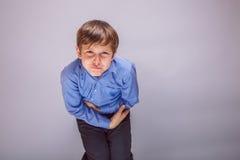 Den buk- tonåringpojken smärtar på grå bakgrund Arkivfoton