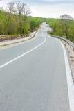 Den buktiga svart asfaltvägen med att markera för vit fodrar från låg poi Royaltyfria Foton