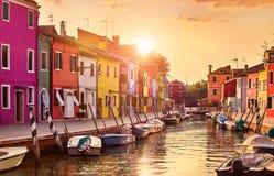 Den Burano ön i Venedig Italien den pittoreska solnedgången över kanalen med fartyg bland gamla färgglade hus stenar gator Arkivbild