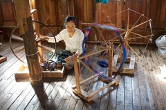 Den Burmese kvinnan är spinnig per lotusblommatråden Royaltyfri Fotografi