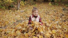Den busiga lilla flickan spelar glatt i en stor hög av gul lövverk Flickan kastar upp gula sidor stock video