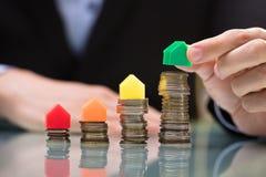 Den BusinesspersonPlacing Green House modellen On Top Of staplade mynt arkivbilder