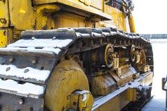 Den Caterpillar traktoren står på snön Arkivbild