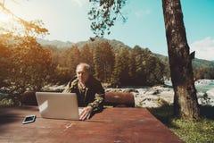 Den Caucasian åldriga skogvaktaren arbetar via bärbara datorn i hans hed arkivfoto