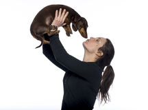 Den Caucasian brunetten rymmer hennes taxhund i luft som ger det en kyss Arkivbilder