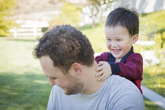 Den Caucasian fadern Having Fun med hans blandade lopp behandla som ett barn sonen Royaltyfri Bild
