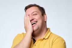Den Caucasian feta mannen skrattar och täcker hans framsida med hans händer royaltyfri fotografi