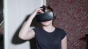 Den Caucasian flickan i VR-exponeringsglas skrämmas, bekymmer om händande försök att ställa in acutance arkivfilmer