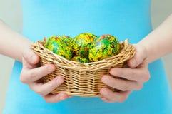 Den Caucasian flickan rymmer i hennes handkorg med påsk målade gula ägg Närbild arkivbilder