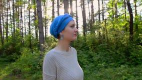 Den Caucasian härliga kvinnan som går i skogen i den blåa turbanen, sol blossar bakom stock video