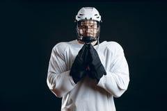 Den Caucasian hockeyspelaren, i likformign som isoleras på svart, ber för bra lycka royaltyfri bild
