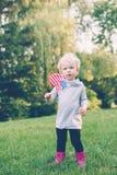 Den Caucasian innehav- och vinkaamerikanska flaggan för flicka parkerar in utvändigt fira 4th begrepp för juli självständighetsda Fotografering för Bildbyråer