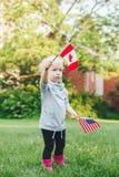 Den Caucasian innehav- och vinkaamerikanska flaggan för flicka parkerar in utvändigt fira 4th begrepp för juli självständighetsda Arkivfoto