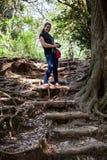 Den Caucasian kvinnan går på stairsteps från rotar av träden i japanträdgård i den Kamakura staden, Japan Royaltyfria Bilder