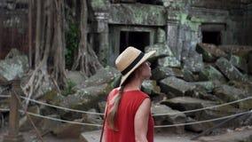 Den Caucasian kvinnan i röd klänning som undersöker, fördärvar av templet för Ta Prohm arkivfilmer