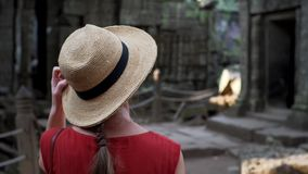 Den Caucasian kvinnan i sugrörhatt går bland fördärvar av Ta Prohm stock video