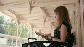 Den Caucasian kvinnan läser en bok på drevet för plattformen för järnvägstationen det väntande på arkivfilmer