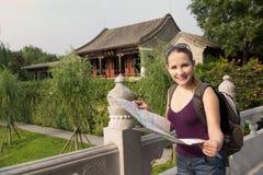 Den Caucasian kvinnan med kartlägger, och ryggsäcken reser i Kina royaltyfri bild