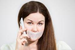 Den Caucasian kvinnan med ledsna ögon och munnen förseglade att kalla mobiltelefonen, grå bakgrund Arkivbild