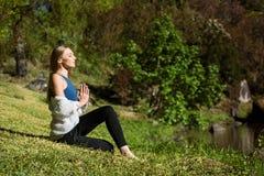 Den Caucasian kvinnan mediterar bredvid floden, händer i namaste royaltyfria bilder
