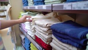 Den Caucasian kvinnan nära shoppar hyllor som väljer handduken i lagercloseup arkivfilmer