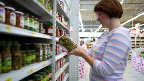 Den Caucasian kvinnan nära shoppar hyllor som väljer marinadgurkor i livsmedelsbutikmarknad lager videofilmer