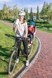 Den Caucasian kvinnan och behandla som ett barn pojken på en cykel Arkivfoto