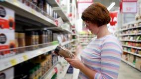 Den Caucasian kvinnan som nära står, shoppar hyllor som väljer ögonblickligt kaffe i livsmedelsbutikmarknad stock video