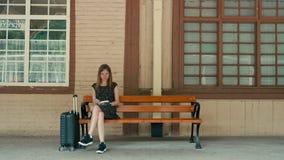 Den Caucasian kvinnan väntar på drevet på stationsplattformen och läsning en bok stock video