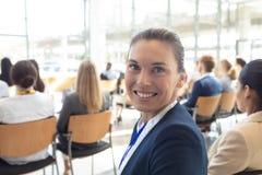 Den Caucasian kvinnliga ledaren satt i konferensrum som ler till kameran arkivbild