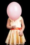 Den Caucasian lilla flickan döljer hennes framsida under ballongen Royaltyfri Bild