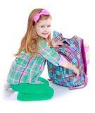 Den Caucasian lilla flickan sätter böckerna i min skola Royaltyfri Fotografi
