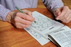Den Caucasian mannen gör sudoku Arkivfoto