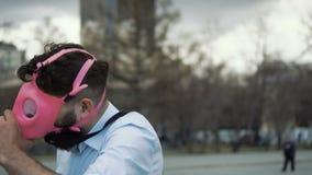 Den Caucasian mannen i en rosa gasmask ropar in i en megafoncloseup Stoppa förorening stock video