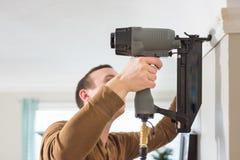 Den Caucasian mannen installerar klippningar med spikar vapnet arkivbild