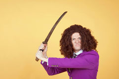 Den Caucasian mannen med afro bärande lilor passar det bärande svärdet royaltyfri bild