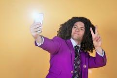 Den Caucasian mannen med afro bärande lilor passar ta en selfie Royaltyfria Foton