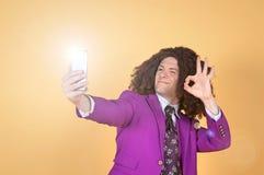 Den Caucasian mannen med afro bärande lilor passar ta en selfie Arkivbild