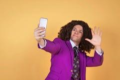 Den Caucasian mannen med afro bärande lilor passar ta en selfie Royaltyfri Fotografi